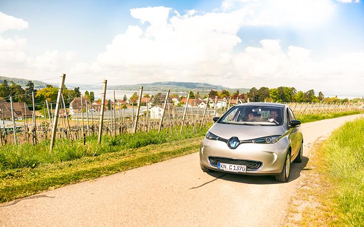 E-Auto fährt durch Weinberge