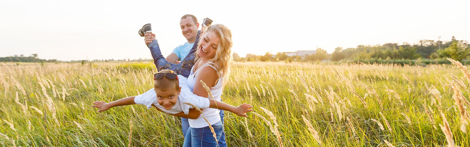 Eltern mit Kind auf einer Wiese