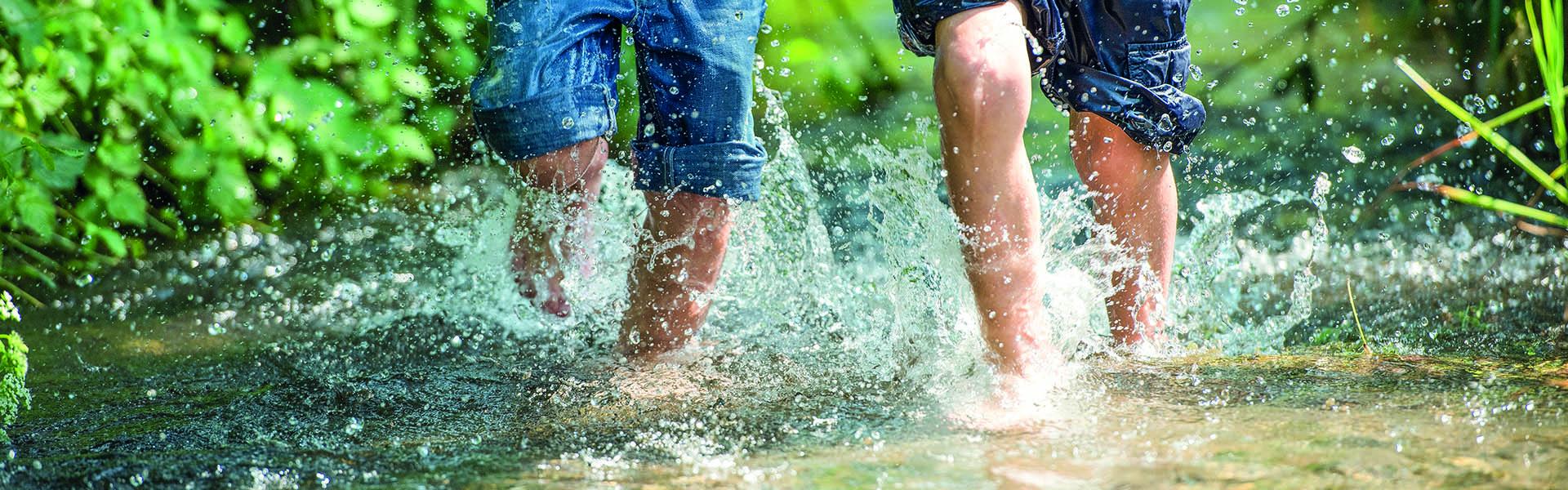 Kinder rennen durch klares Wasser eines Bachs.