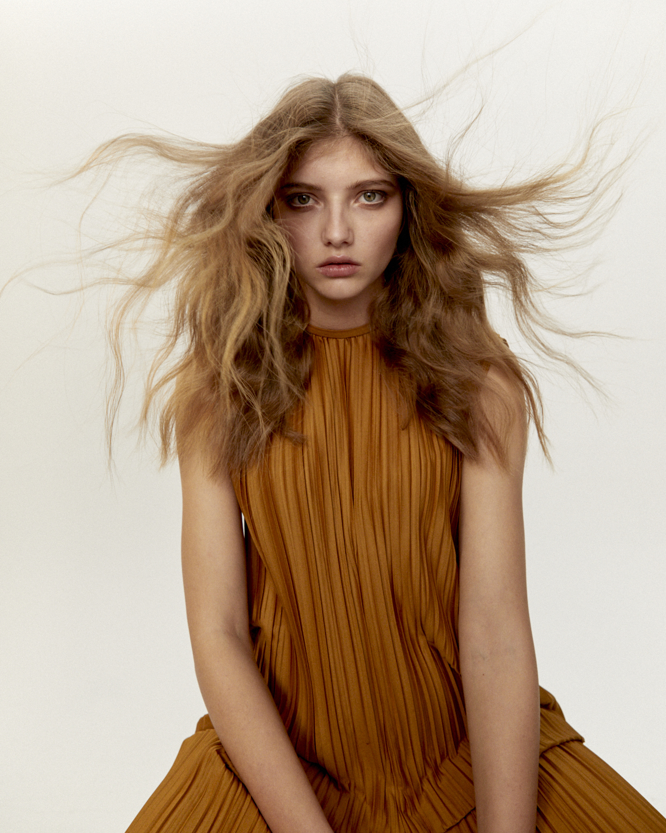 Girl with a long hair editorial hairstyle and soft waves blown off the face. Strawberry blonde hair colour
