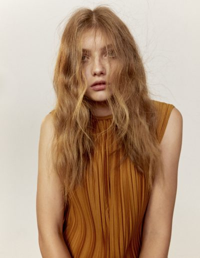 Girl with long hair editorial hairstyle and soft waves styled messy and on the face. Strawberry blonde hair colour