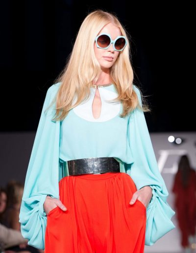 Girl on a fashion runway with wavy sixties hairstyle with a middle part and golden blonde colour hair