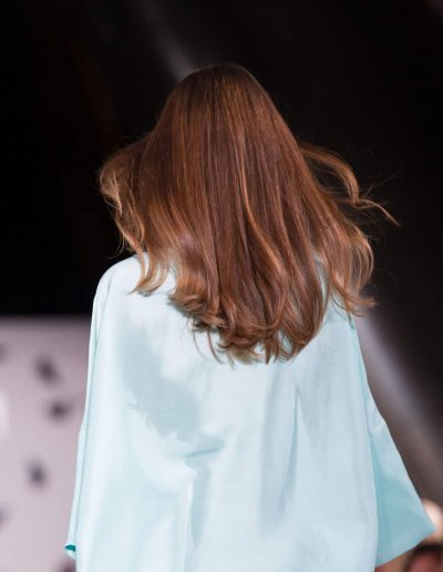 Girl on a fashion runway with wavy hairstyle and brown colour hair