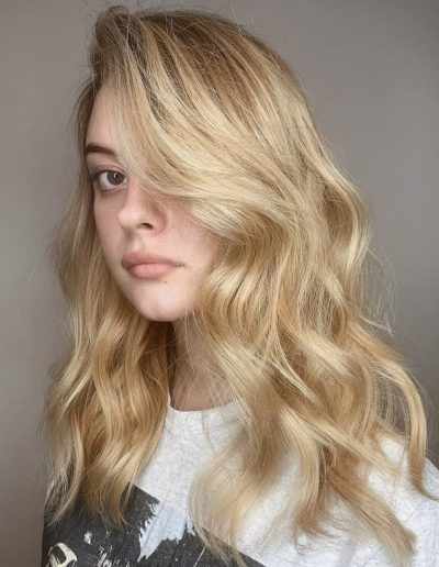 Girl with golden blonde hair painting and long layered haircut with curly hairstyle at Headcase Hair Potts Point Sydney