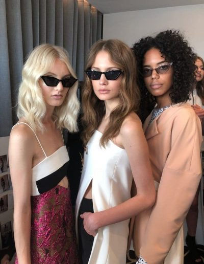 Fashion Week Sydney Australia backstage image of three models with center part hairstyles and wavy hair with bleach blonde and brunette hair colours