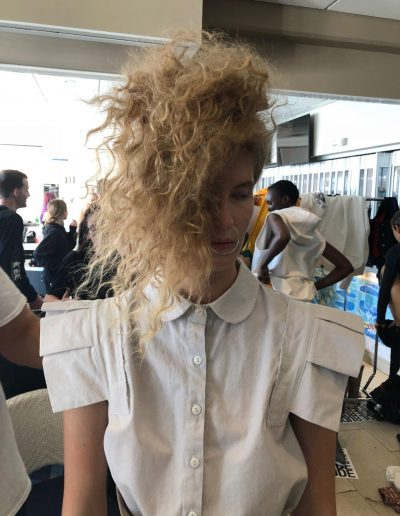 Fashion Week Sydney Australia backstage image of model with messy curly upstlye hairstyle and blonde hair colour