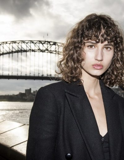 Fashion Week Sydney Australia Girl with curly long bob Lob Haircut with curly fringe with soft brown sun kissed hair colour standing in front of Sydney Harbour Bridge