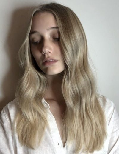 Girl with blonde balayage and face frame highlights with long hair, soft wavy hairstyle and long layered haircut