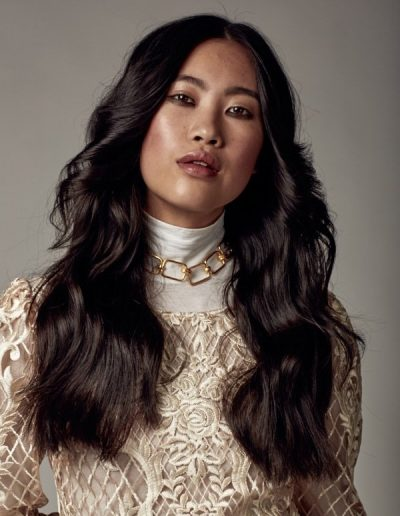Vogue Australia image of girl with long hair styled in soft waves flicked back in a 70's hair inspiration hairstyle with long dark brunette asian hair