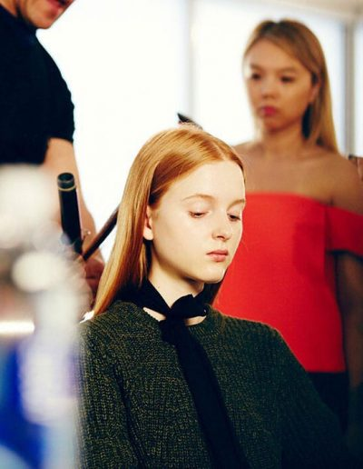 Fashion week New York image of a girl with a center part hairstyle, long hair styled with soft waves and copper red hair colour
