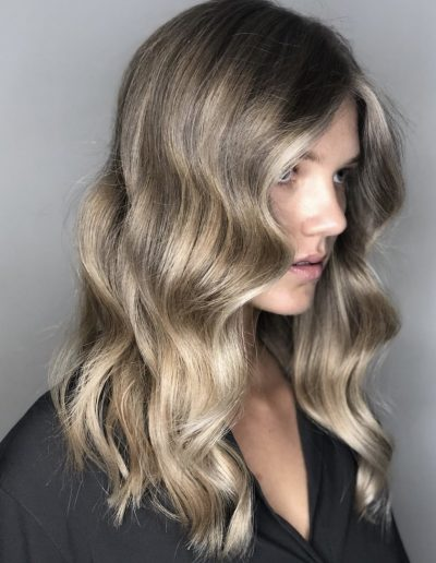 Girl with Natural balayage hair colour with face frame highlights and a long layered haircut with a soft wavy hairstyle