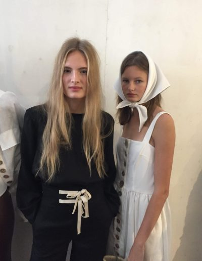 Australian Fashion Week Sydney models posing backstage with soft wavy hairstyles. One model has blonde natural balayage with face frame highlights and the other is wearing a hair accessory