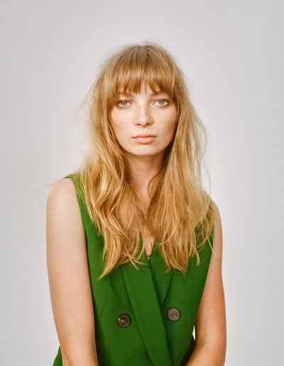 Girl with a strong hair fringe and layered haircut with golden blonde balayage. Hairstyle in soft waves