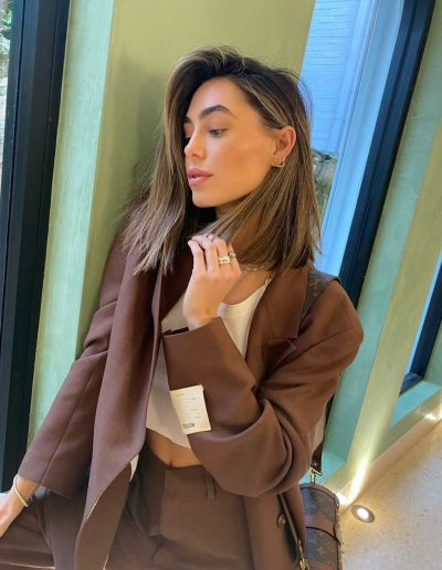 Megan Mackenzie with natural balayage bronde hair colour. Haircut in a long bob lob haircut and hairstyle straight with a strong side part