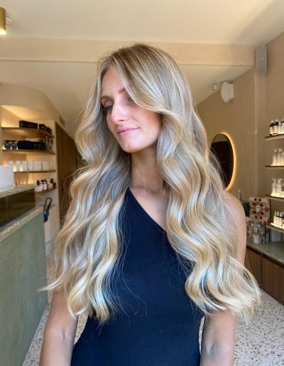 Girl with long hair and a wavy center part hair style with blonde hair with highlights and blonde balayage hair colour standing in Headcase Hair Salon Sydney