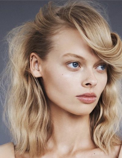 Girl with blonde hair with natural highlights and a 70's inspired hairstyle with a flick and soft waves