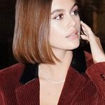 Kaia Gerber with a long bob haircut also called a Lob and soft brunette hair colour. Straight center part hairstyle