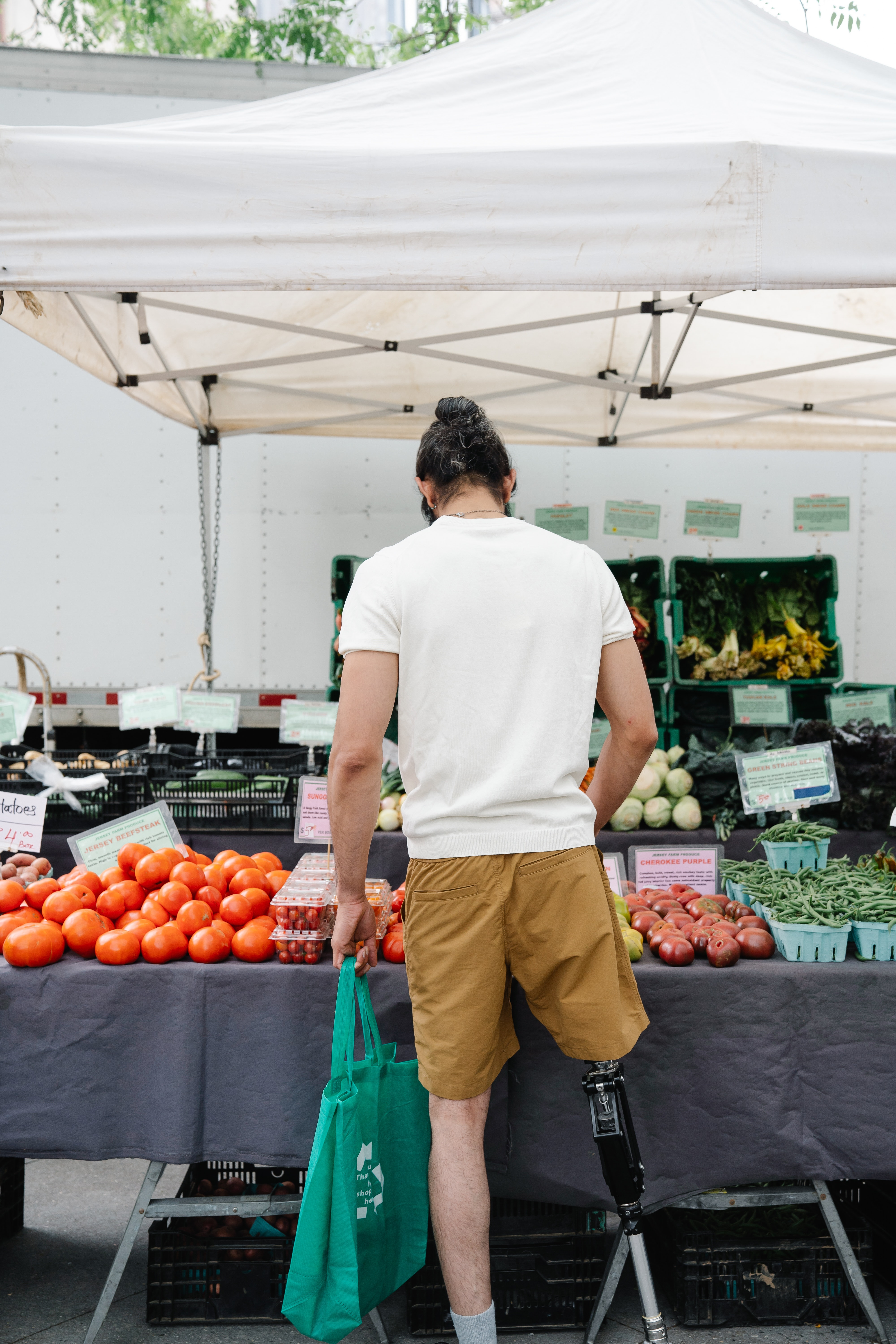 Man with a prosthetic leg standing in front of Fruit Stand