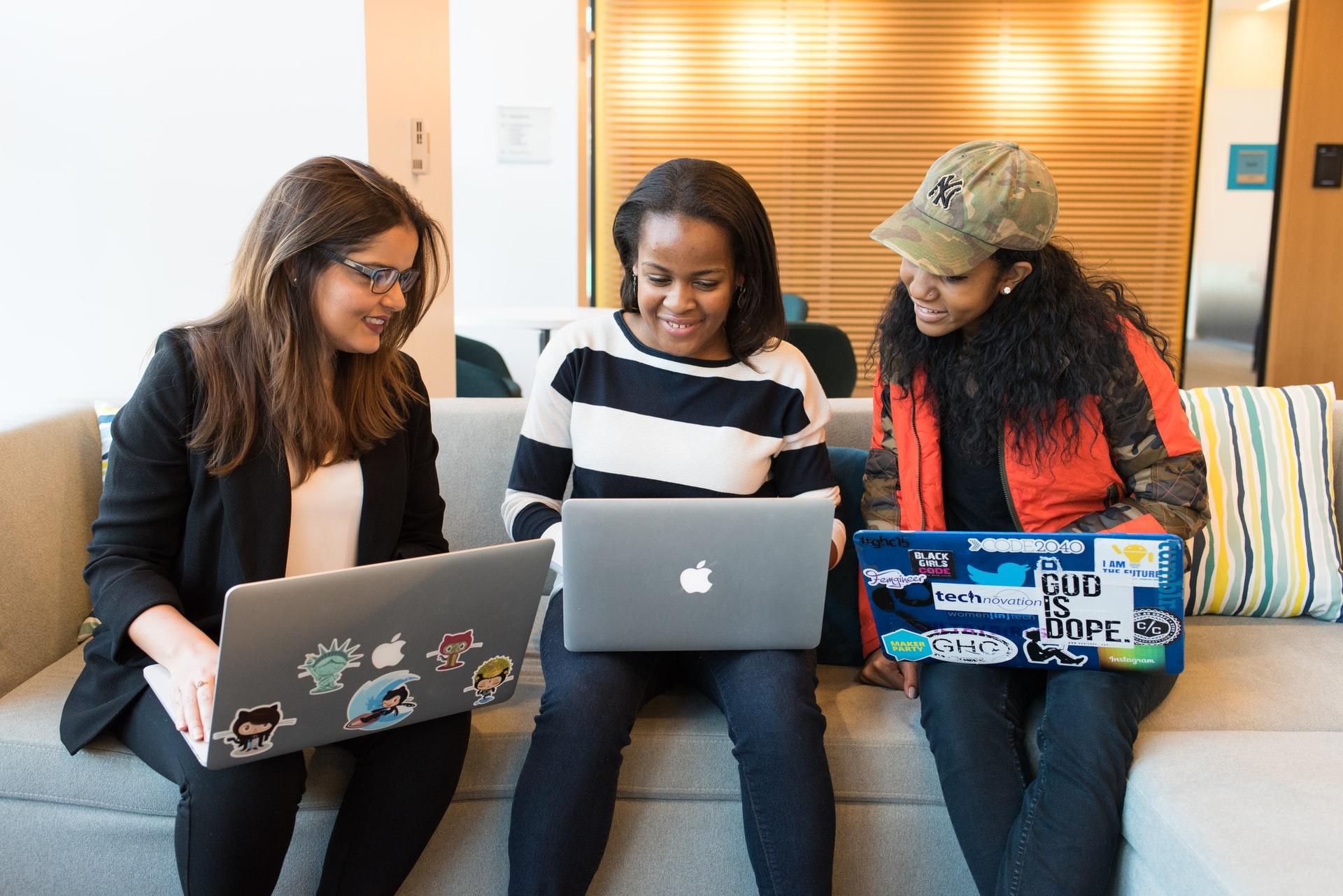 Three women working around a computer in an office.