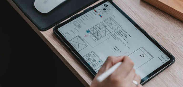 Image of UI designer writing on digital pad.