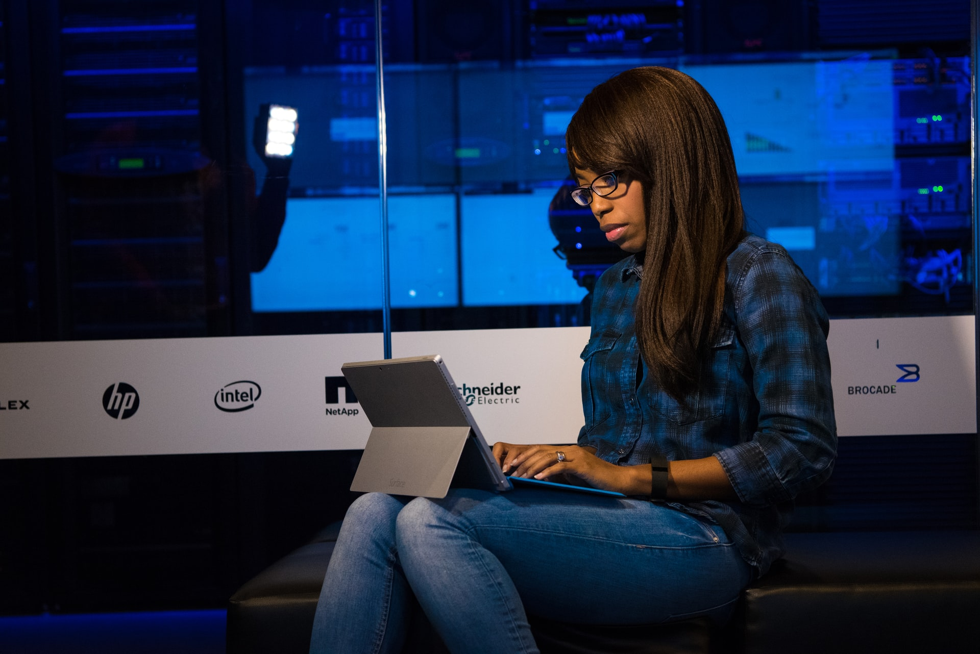 Woman in blue and black plaid using a tablet.