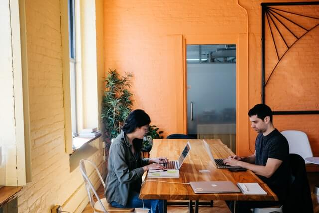 A man and woman working together at a wooden desk.