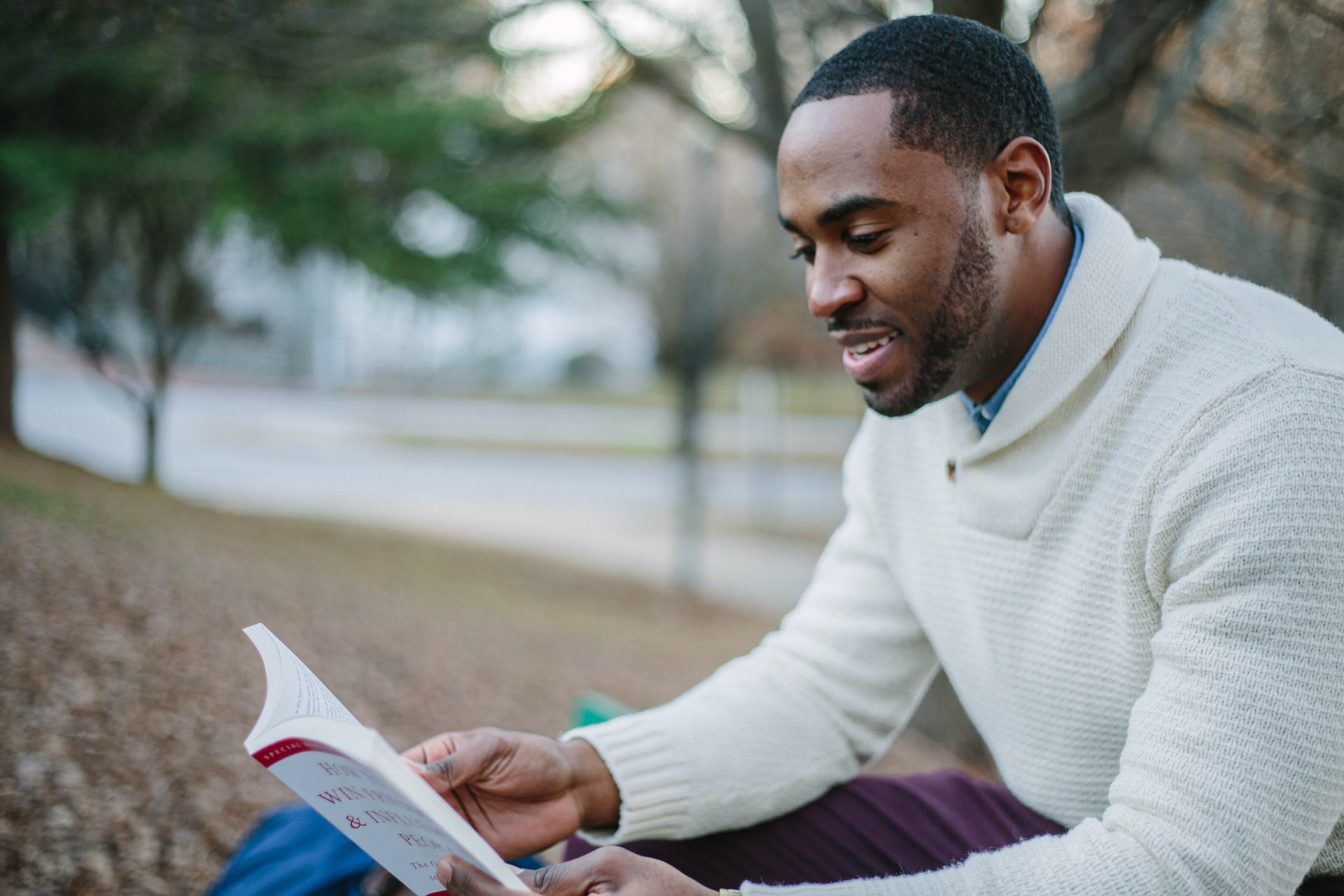 A man wearing a white sweater reads a book in the park.