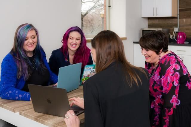 Four women look at a laptop on a brown table.
