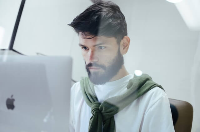 Man with a green scarf working at a computer.