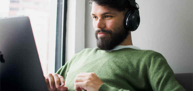 A man wearing a green shirt and headphones works on a laptop.