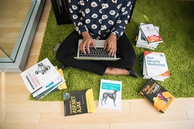 A woman sits among books while working on a laptop.