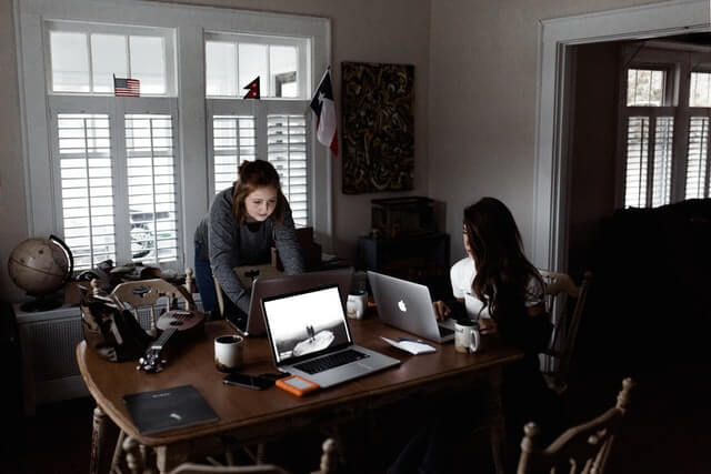 Two women working on laptops on a brown table.