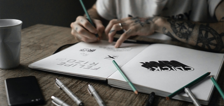 A guy drawing logos on his notepad