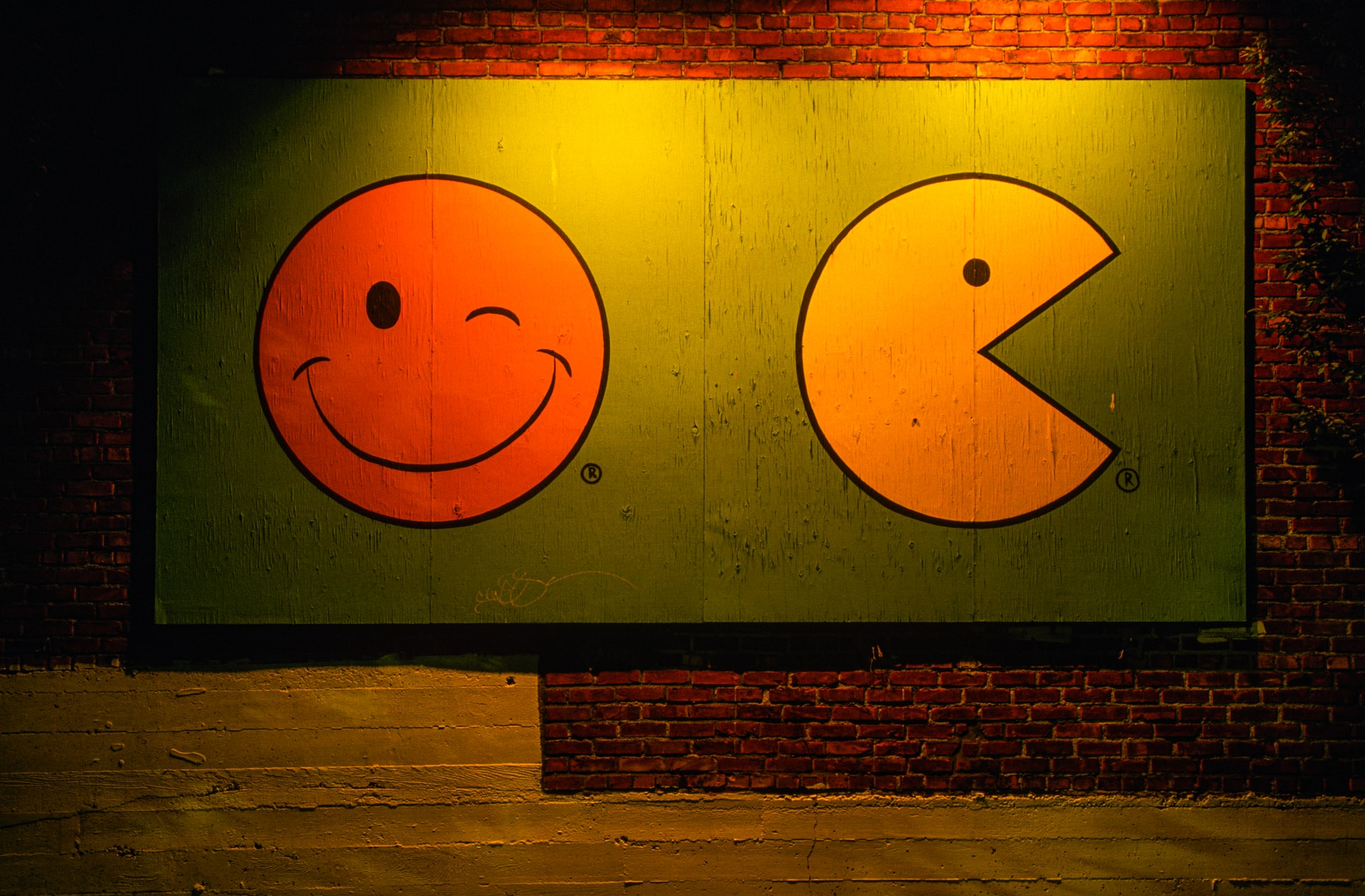 A red and yellow smiley face are painted against a green background.