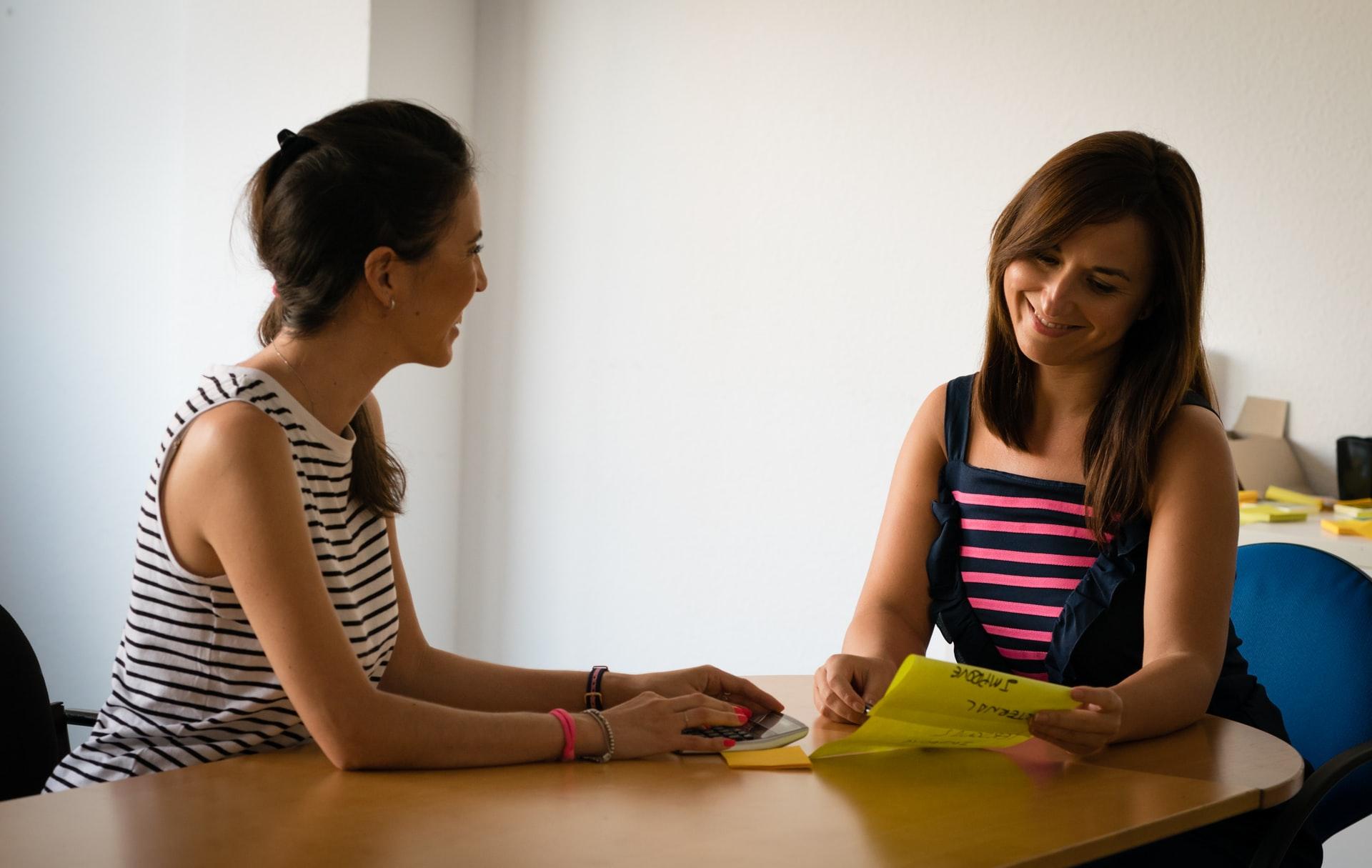 Two women sit at a desk.