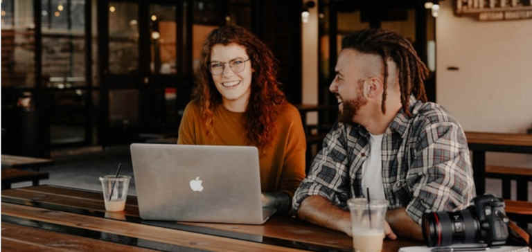 A man and a woman sit at a table with a laptop and a camera.
