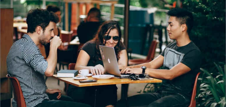 Two men and a woman sit at a coffee shop with a laptop.