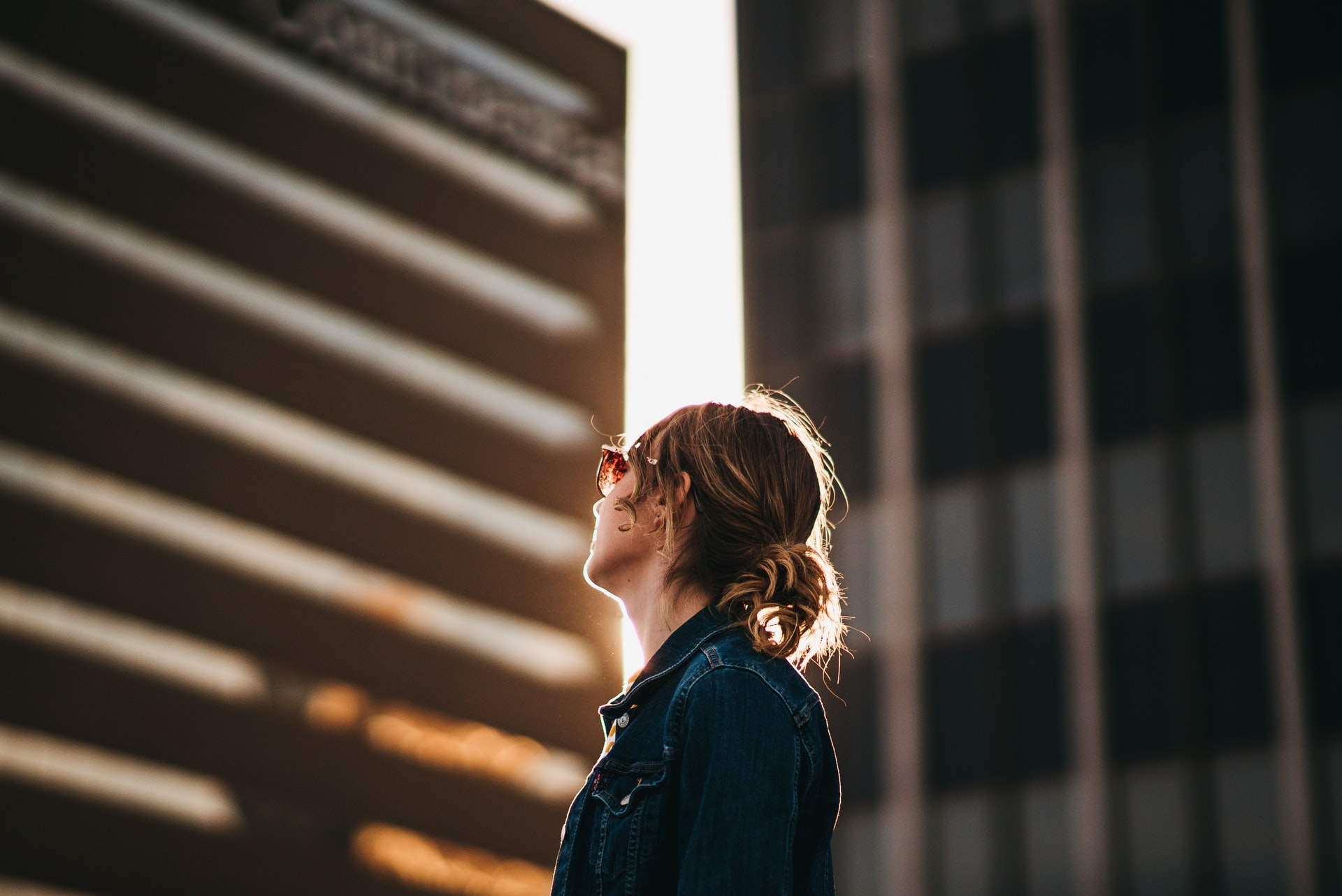A woman in a jean jacket looks up at a tall building.