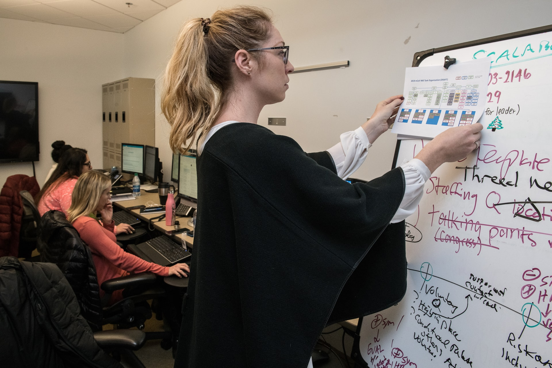 A woman wearing a black shirt posts a graph on a whiteboard.
