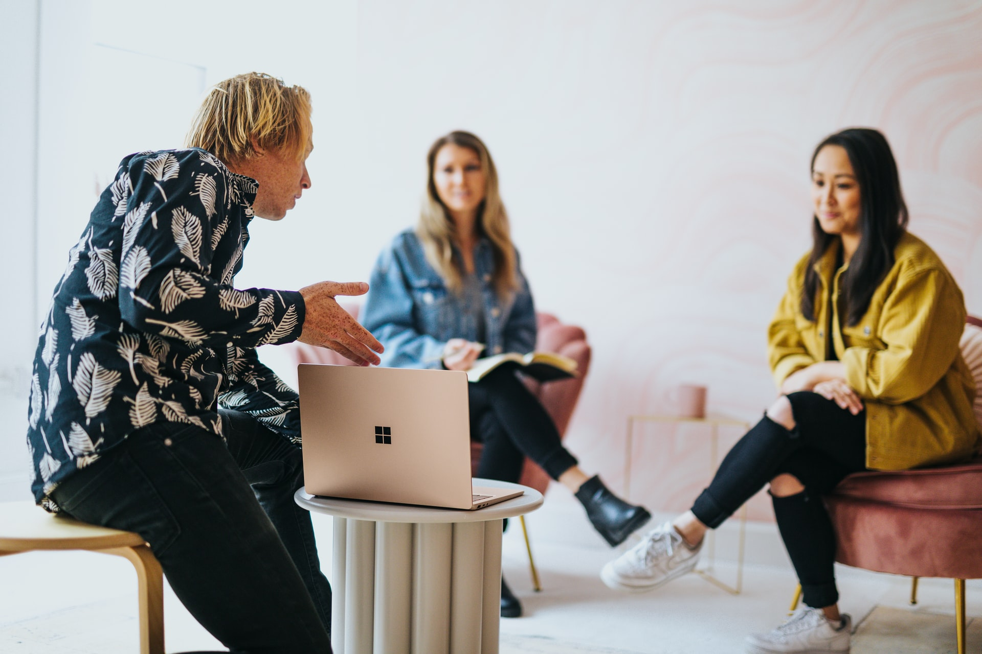 A man and two women discuss ideas during a business meeting.