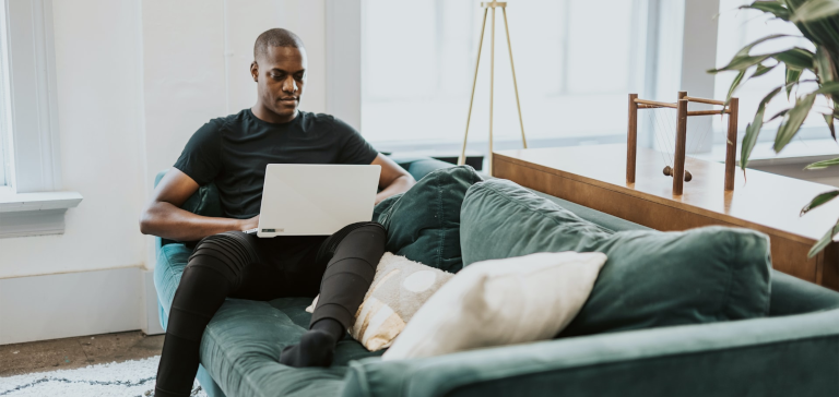 A man wearing a black shirt sits on a couch and works on a laptop.