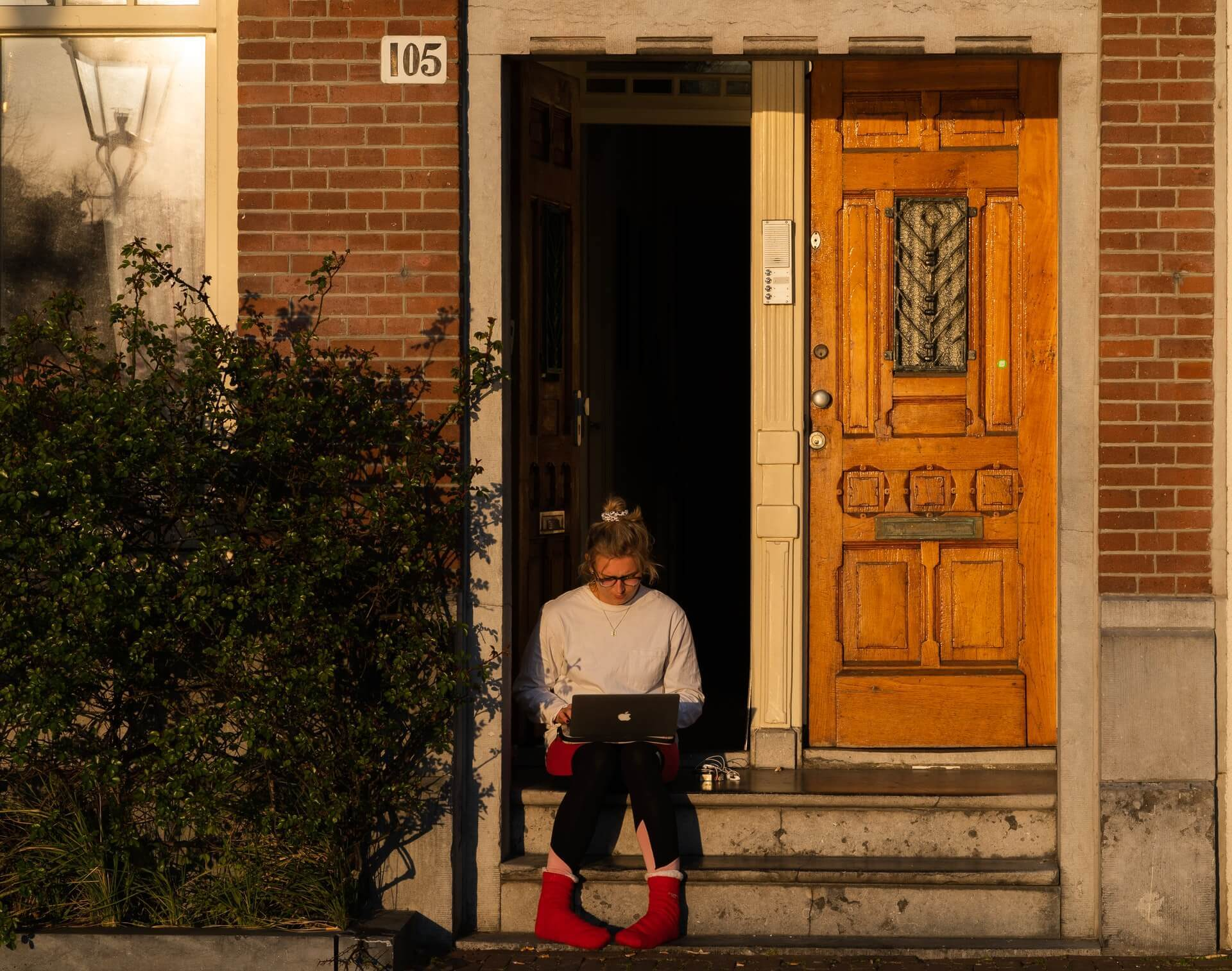 A woman in red socks and a grey sweater works on a laptop outside.