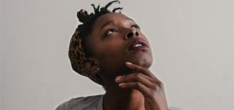 A woman in a gray shirt looks up as she is thinking.