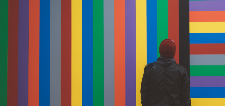 Alt Tag: A man in a red beanie looks up at a colorful wall.