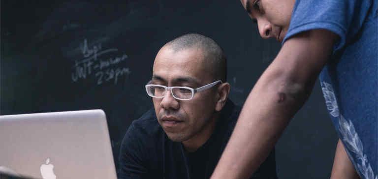 Two men work on a Macbook laptop.