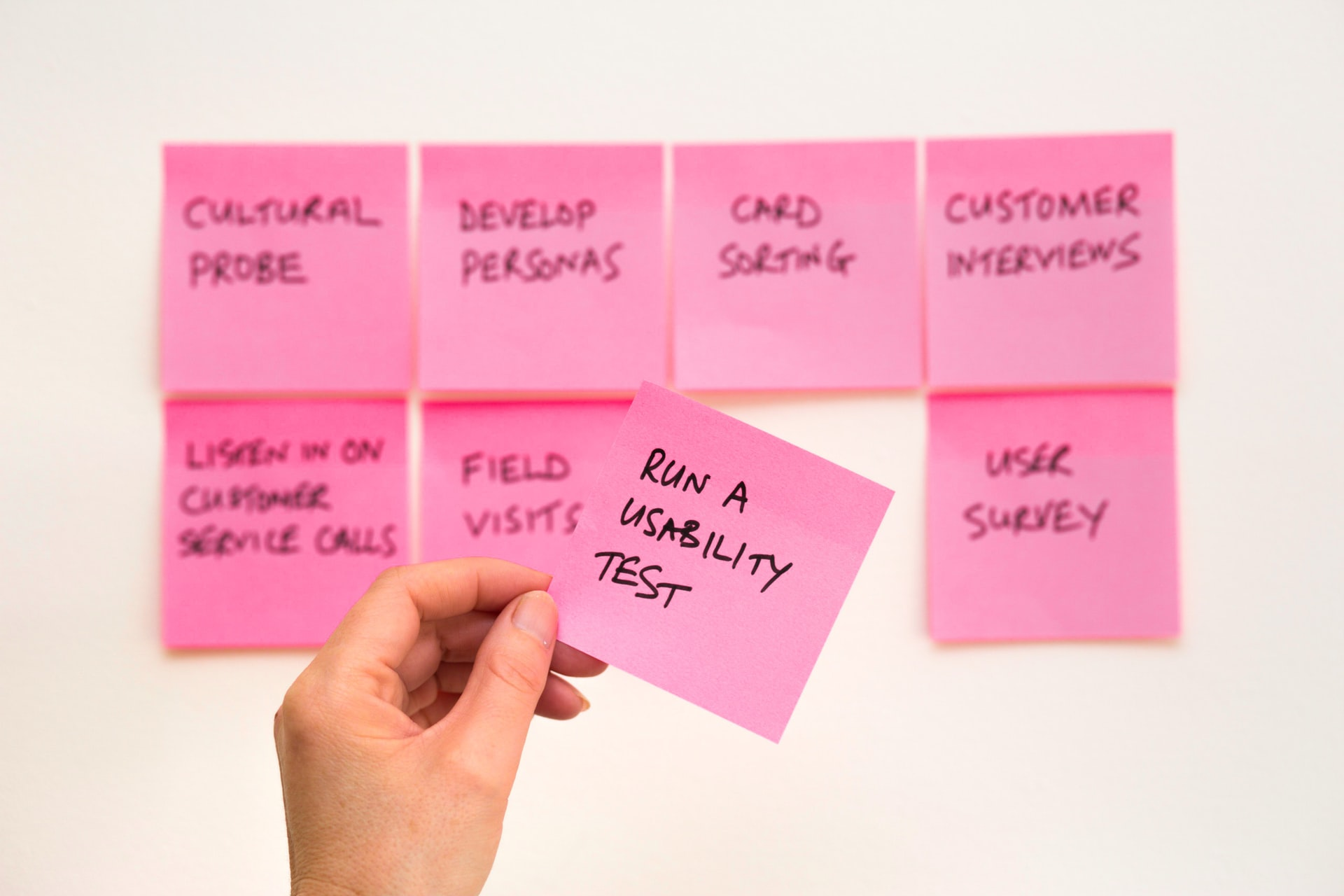 A person holding a pink sticky note.