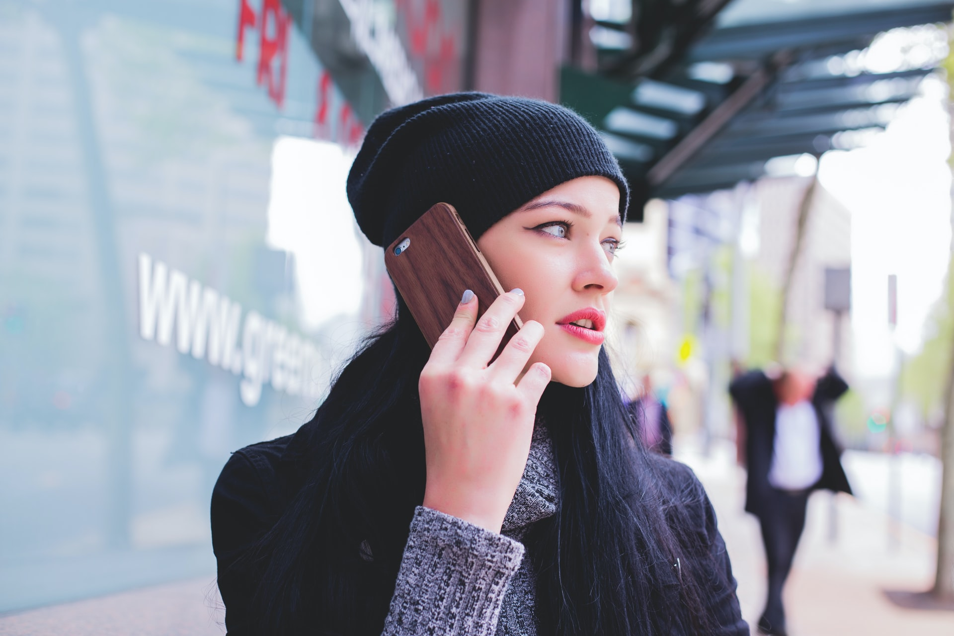A woman wearing a beanie talks into a smartphone.