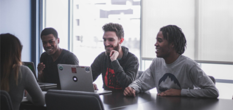 Three men with laptops sit across from a woman at a table.