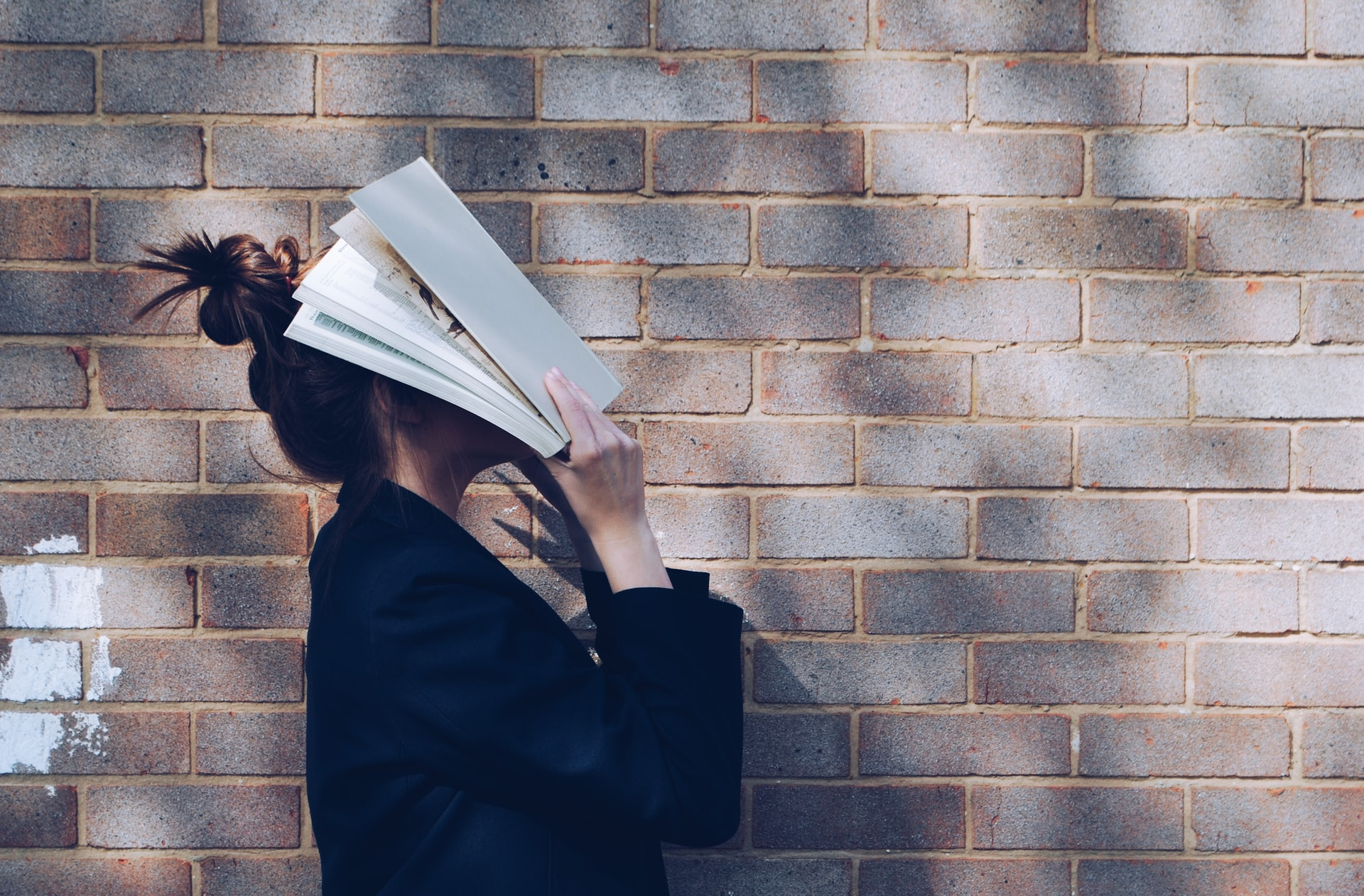 A girl holds a book over her face near a brick wall.