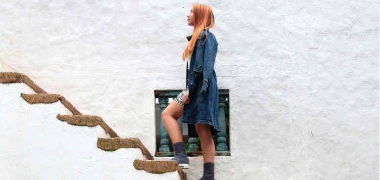 A redheaded woman climbs a staircase.